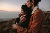 Romantic young couple standing in mountain together and looking at view. Young man embracing his girlfriend and looking away.