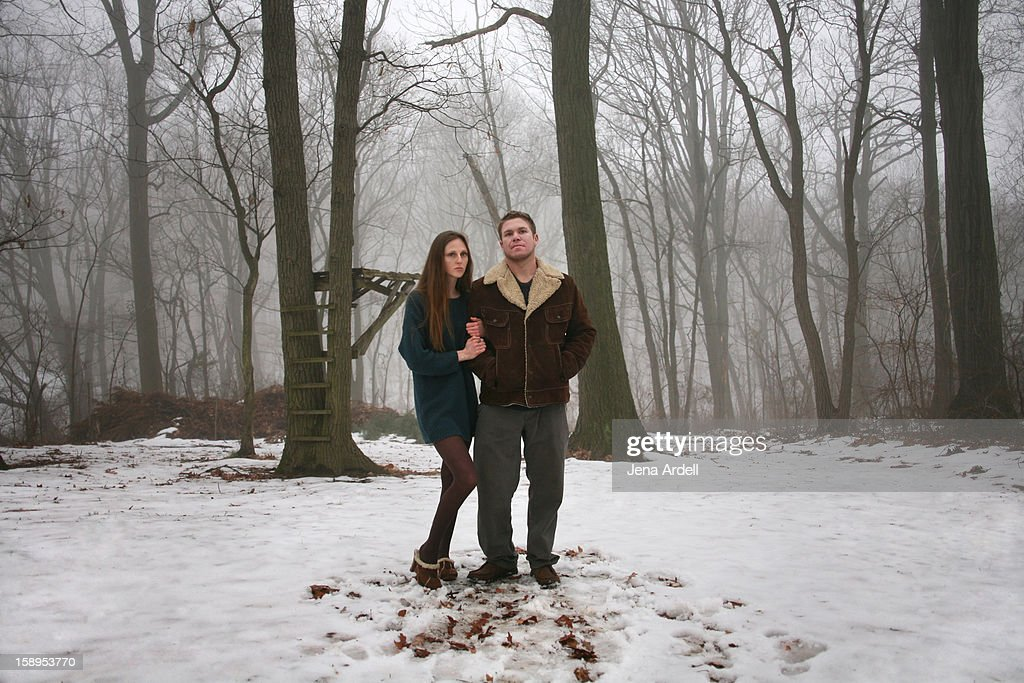 Romantic young couple standing in snow & fog : Stock Photo