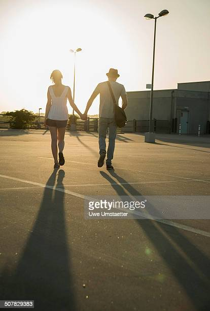 Romantic young couple strolling hand in hand across empty parking lot