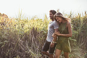 Outdoor shot of romantic young couple walking together in countryside. Young man and woman on a holiday.