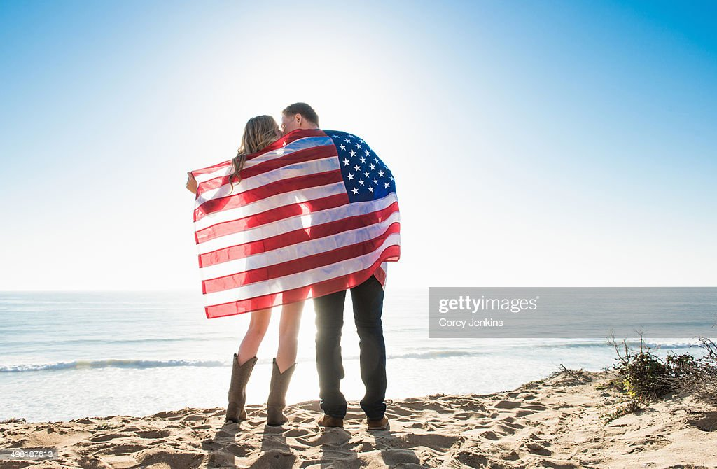 Romantic young couple wrapped in american flag, Torrey Pines, San Diego, California, USA