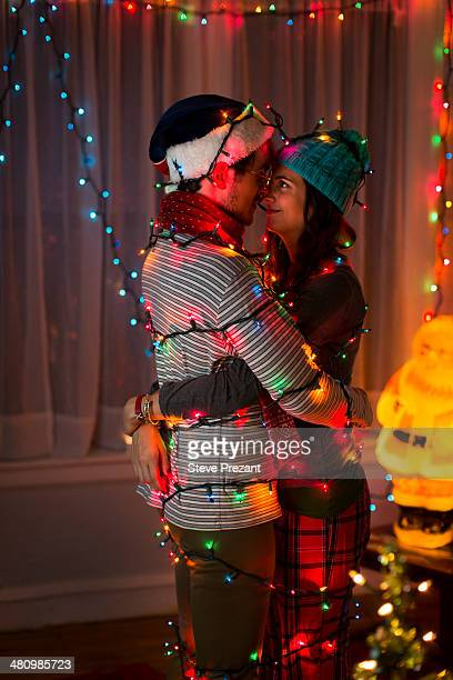 Romantic young couple wrapped in fairy lights at christmas