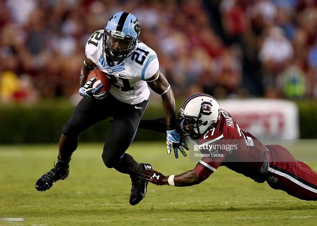 Romar Morris #21 of the North Carolina Tar Heels tries to get past Victor Hampton #27 of the South Carolina Gamecocks during their game at Williams-Brice Stadium on August 29, 2013 in Columbia, South Carolina.