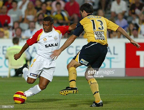 Romario of Adelaide runs at Tony Vidmar of the Mariners during the round fourteen Hyundai ALeague match between the Central Coast Mariners and...