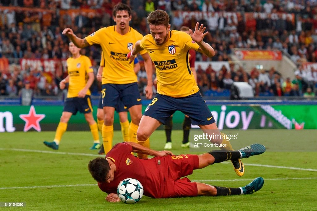TOPSHOT - Roma's Argentinian forward Diego Perotti (Bottom) dalls under pressure from Atletico Madrid's midfielder Saul Niguez during the UEFA Champions League Group C football match between AS Roma and Atletico Madrid on September 12, 2017 at the Olympic stadium in Rome. / AFP PHOTO / Andreas SOLARO