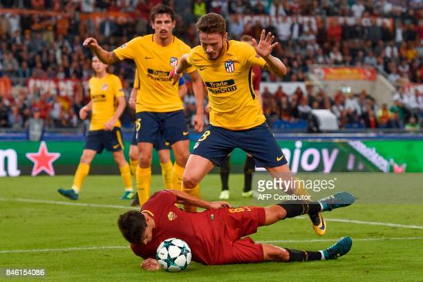TOPSHOT Roma's Argentinian forward Diego Perotti dalls under pressure from Atletico Madrid's midfielder Saul Niguez during the UEFA Champions League...