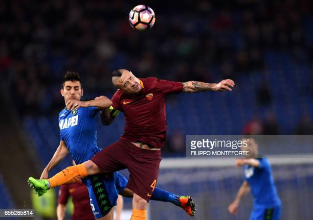 TOPSHOT Roma's Belgian midfielder Radja Nainggolan and Sassuolo's defender Luca Antei go for a header during the italian Serie A football match Roma...