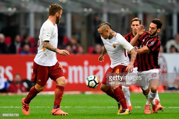 AS Roma's Belgium midfielder Radja Nainggolan vies with AC Milan's German midfielder Hakan Calhanoglu during the Italian Serie A football match AC...