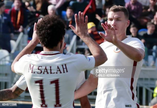 Roma's Bosnian forward Edin Dzeko celebrates after scoring with teammate Egyptian forward Mohamed Salah during the Italian Serie A football match FC...