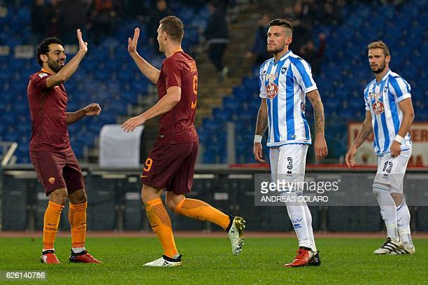 AS Roma's Bosnian forward Edin Dzeko flanked by Pescara's players celebrates with his teammates Egyptian midfielder Mohamed Salah after scoring a...