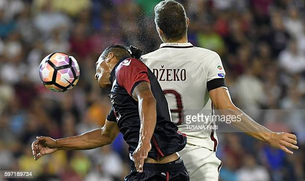 Roma's Bosnian forward Edin Dzeko vies for the ball with Cagliari's defender Bruno Alves during the Serie A football match between Cagliari and Roma...