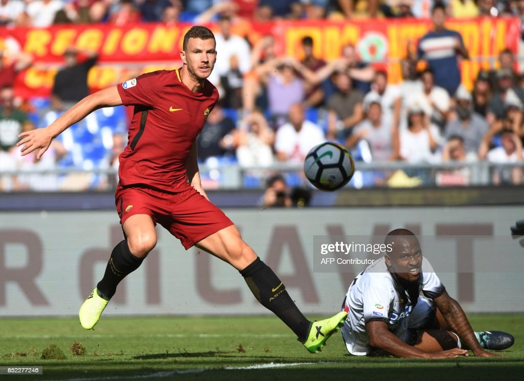 AS Roma's Bosnian forward Edin Dzeko (L) vies with Udinese's Brazilian defender Caetano de Souza Santos Samir (R) during the Italian Serie A football match between AS Roma and Udinese on September 23, 2017 at the Olympic stadium in Rome. / AFP PHOTO / Vincenzo PINTO
