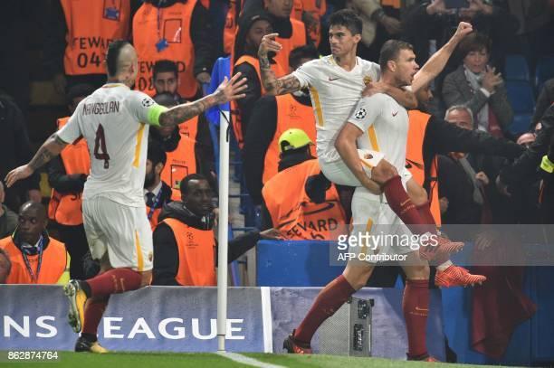 Roma's Bosnian striker Edin Dzeko celebrates after scoring with Roma's Argentinian midfielder Diego Perotti and Roma's Belgian midfielder Radja...
