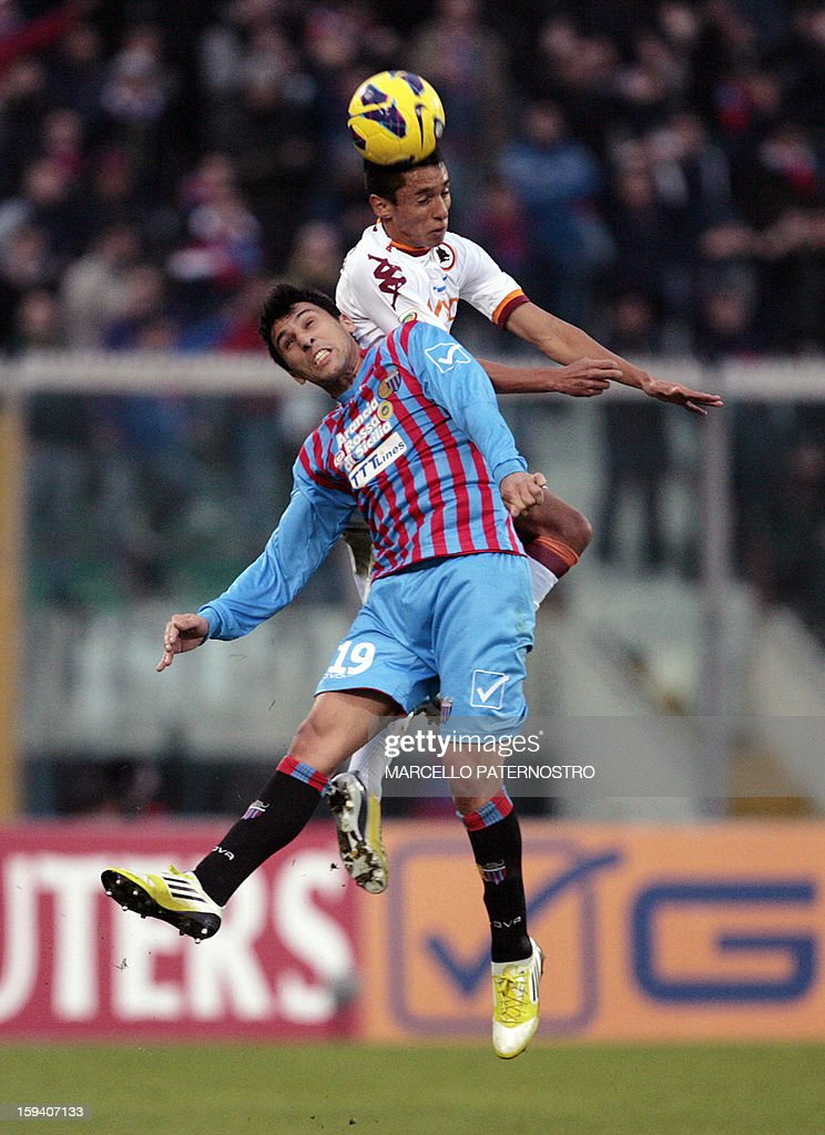 AS Roma's Brazilian defender Aoas Marquinho (top) vies with Catania's Argentinian midfielder Lucas Castro during an Italian Serie A football match at Massimino Stadium on January 13, 2013 in Catania. AFP PHOTO / Marcello PATERNOSTRO