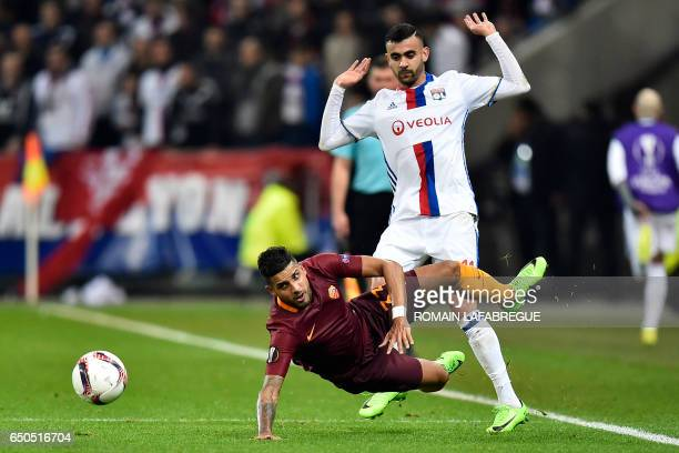 Romas Brazilian defender Emerson Palmieri is tackled by Lyon's Algerian forward Rachid Ghezzal during the Europa League round of 16 first leg...