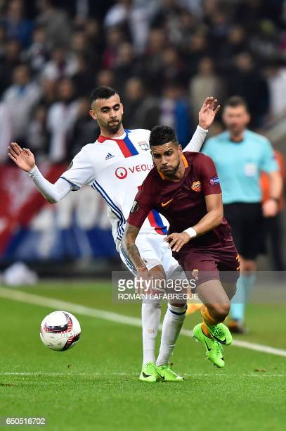 Romas Brazilian defender Emerson Palmieri vies with Lyon's Algerian forward Rachid Ghezzal during the Europa League round of 16 first leg football...