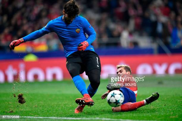Roma's Brazilian goalkeeper Alisson blocks a shot on goal by Atletico Madrid's French forward Antoine Griezmann during the UEFA Champions League...