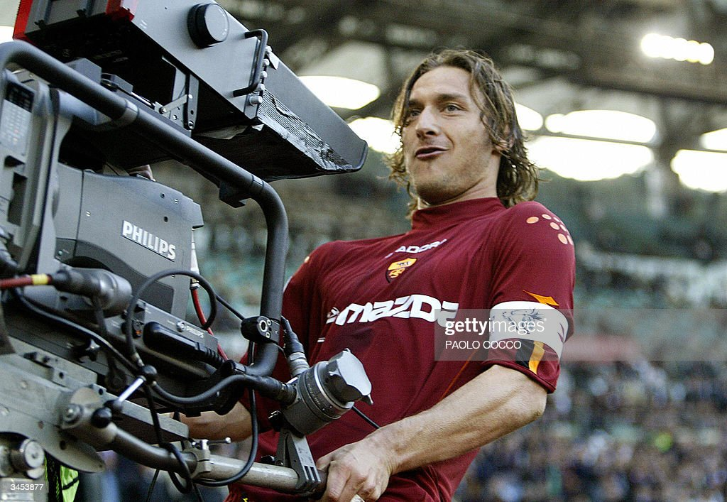 AS Roma's captain <a gi-track='captionPersonalityLinkClicked' href=/galleries/search?phrase=Francesco+Totti&family=editorial&specificpeople=208985 ng-click='$event.stopPropagation()'>Francesco Totti</a> celebrates with a tv camera after scoring against Lazio during their Serie A soccer match at Rome's Olympic stadium 21 April 2004.