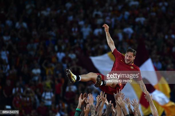 TOPSHOT Roma's Captain Francesco Totti is tossed in the air by his teammates during a ceremony following his last match with AS Roma after the...