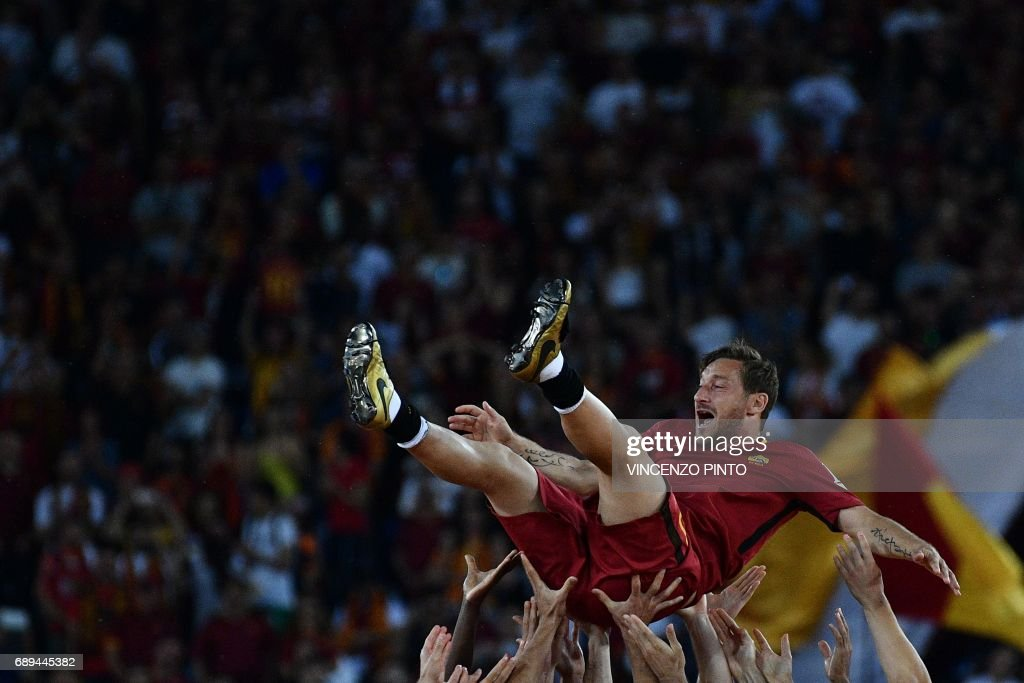 AS Roma's Captain Francesco Totti is tossed in the air by teammates during a ceremony following his last match with AS Roma after the Italian Serie A football match AS Roma vs Genoa on May 28, 2017 at the Olympic Stadium in Rome. Italian football icon Francesco Totti retired from Serie A after 25 seasons with Roma, in the process joining a select group of 'one-club' players. / AFP PHOTO / Vincenzo PINTO