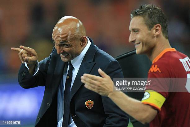 Roma's coach Luciano Spaletti gestures flanked by Roma's forwards and captain Francesco Totti at the end of the 'Tim Super Cup' trophy after...