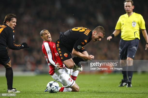 Roma's Daniele De Rossi is fouled by Arsenal's Gael Clichy as they battle for the ball Referee Claus Bo Larsen looks on