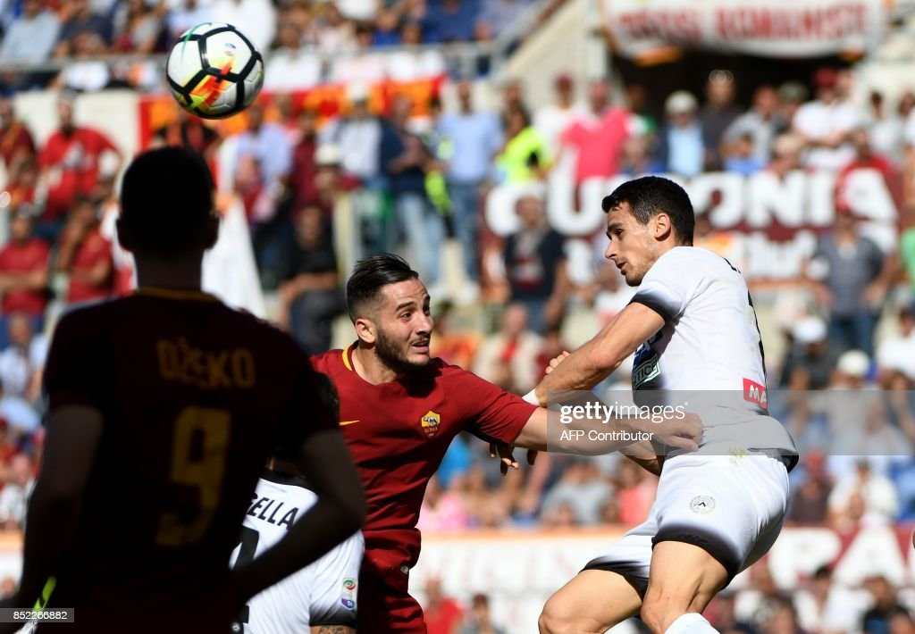 AS Roma's defender from Greece Kostas Manolas (C) and Udinese forward Kevin Lasagna (R) go for a header during the Italian Serie A football match AS Roma vs Udinese on September 23, 2017 at the Olympic stadium in Rome. / AFP PHOTO / Vincenzo PINTO