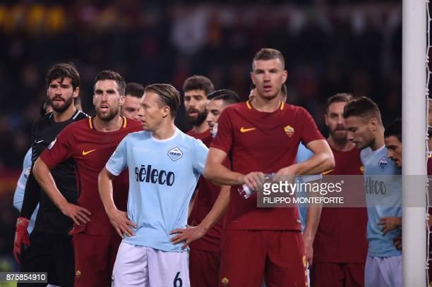 Roma's Dutch midfielder Kevin Strootman and Roma's Brazilian goalkeeper Alisson look on during the Italian Serie A football match AS Roma vs Lazio on...