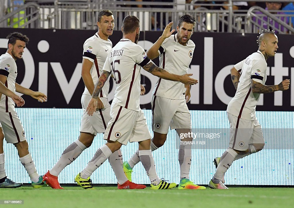 Roma's Dutch midfielder Kevin Strootman celebrates with his teammates after scoring a goal during the Serie A football match between Cagliari and...