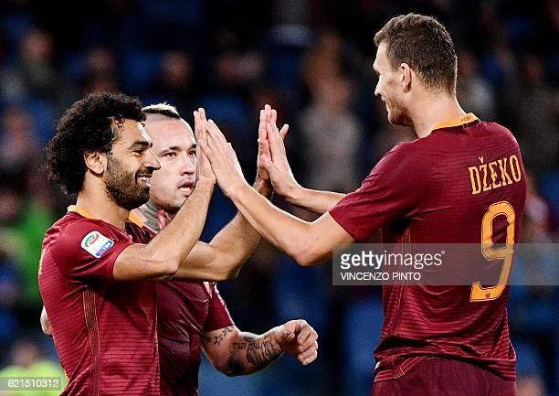 AS Roma's Egyptian forward Mohamed Salah celebrates with teammates AS Roma forward of Bosnia Edin Dzeko and AS Roma's midfielder of Belgium Radja...