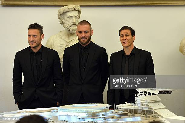 AS Roma's forward Francesco Totti AS Roma's midfielder Daniele De Rossi and AS Roma's French coach Rudi Garcia pose in front a model of the Rome's...