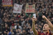 Roma's forward Francesco Totti celebrates by taking a 'selfie' with fans after scoring a second goal during the Italian Serie A football match on...