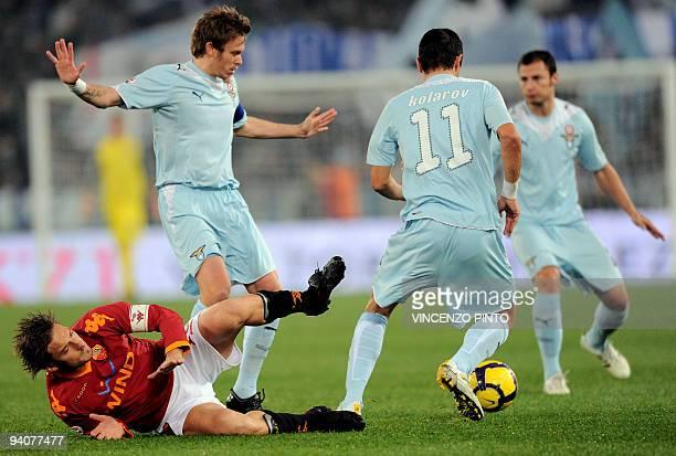AS Roma's forward Francesco Totti is takled by Lazio's midfielder Roberto Baronio in front of Lazio's Serbian defender Aleksandar Kolarov during...