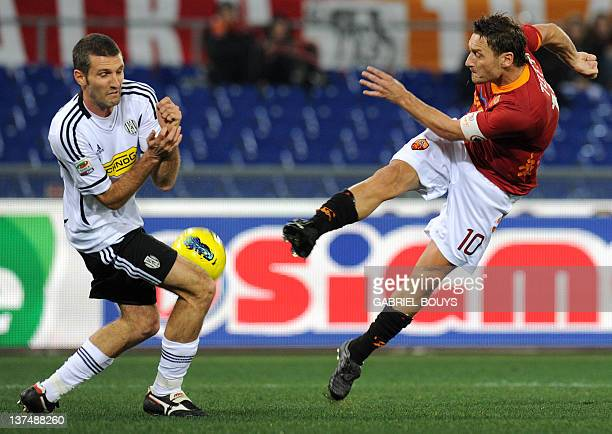 AS Roma's forward Francesco Totti kicks the ball in front of Cesena defender Maurizio Lauro during the Italian Serie A football match between AS Roma...