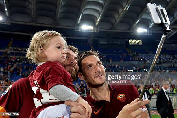 AS Roma's forward Francesco Totti takes a selfie with Roma's forward Daniele De Rossi and his child at the end of the Italian Serie A football match...