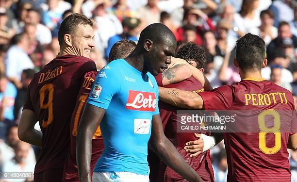 Roma's forward from Bosnia and Herzegovina Edin Dzeko celebrates with teammates after scoring as Napoli's defender Kalidou Koulibaly looks dejected...