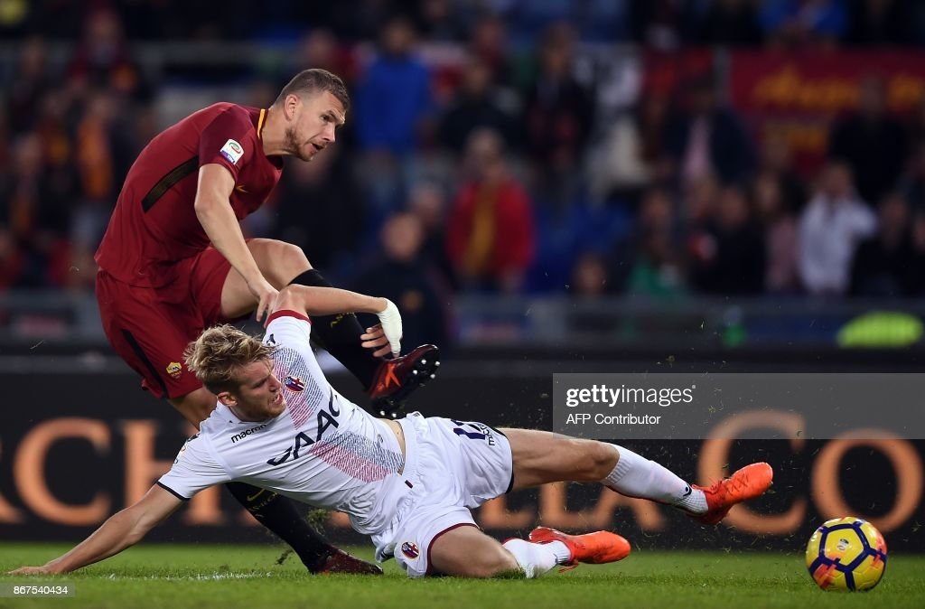 Roma's forward from Bosnia Erzegovina Edin Dzeko (L) vies with Bologna's Swedish defender Filip Helander during the Italian Serie A football match Roma vs Bologna on October 28, 2017 at the Olympic Stadium in Rome. /
