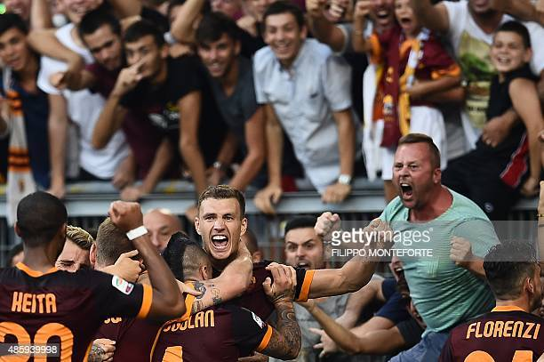 Roma's forward from BosniaHerzegovina Edin Dzeko celebrates with teammates and fans after scoring during the Italian Serie A football match AS Roma...