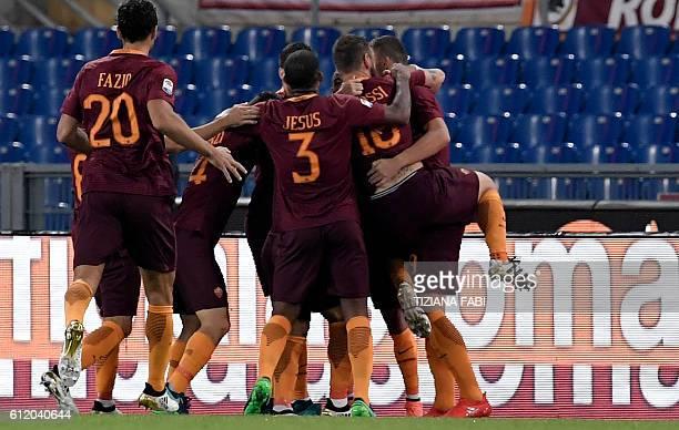 Roma's forward from BosniaHerzegovina Edin Dzeko celebrates with teammates after scoring during the Italian Serie A football match AS Roma vs Inter...