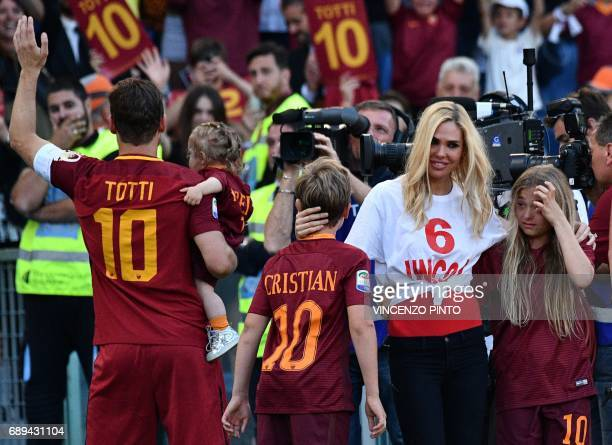Roma's forward from Italy Francesco Totti greets fans as he holds his daughter Isabel next to the others chidren Chanel Cristian and his wife Ilary...