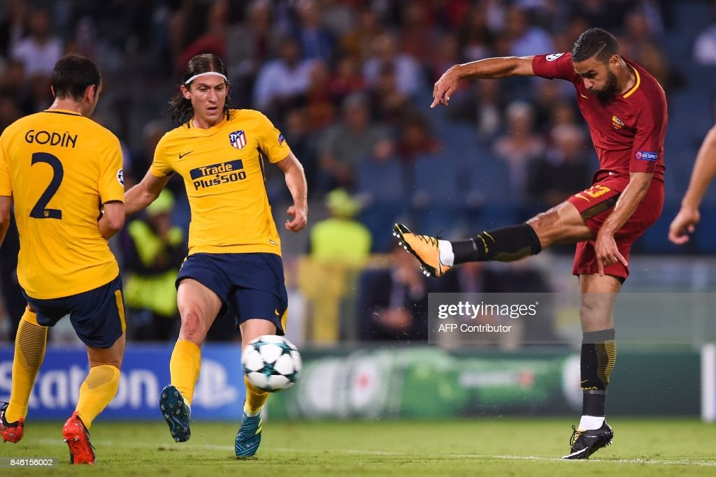 Roma's French forward Gregoire Defrel (R) shoots on goal past Atletico Madrid's Brazilian defender Filipe Luis (C) and Atletico Madrid's Uruguayan defender Diego Godin during the UEFA Champions League Group C football match between AS Roma and Atletico Madrid on September 12, 2017 at the Olympic stadium in Rome. / AFP PHOTO / Filippo MONTEFORTE