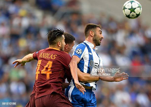 AS Roma's Greek defender Kostas Manolas vies with Porto's Spanish forward Adrian Lopez during the UEFA Champions League first leg play off football...