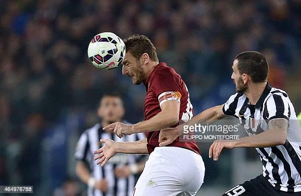 Roma's Italian forward Francesco Totti heads the ball next to Juventus' Italian defender Leonardo Bonucci during the Italian Serie A football match...