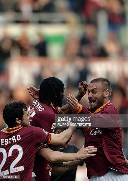 AS Roma's Italian forward Francesco Totti is congratulated by teammates Mattia Destro Gervinho and Daniele De Rossi after scoring against Parma...