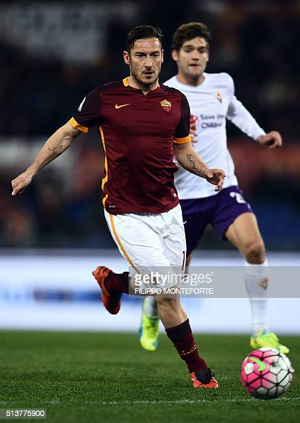 Roma's Italian forward Francesco Totti vies with Fiorentina's Spanish defender Marcos Alonso Mendoza during the Italian Serie A football match AS...