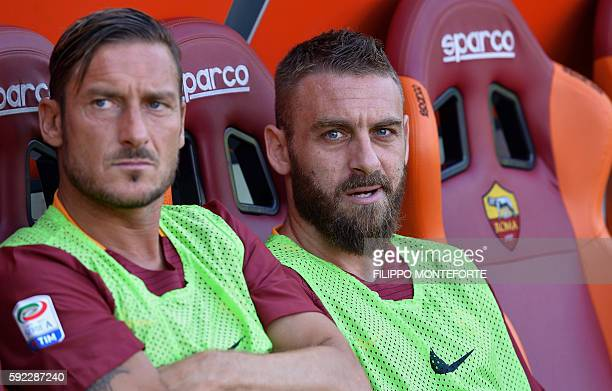 Roma's midfielder Daniele De Rossi and forward Francesco Totti look on from the bench during the Italian Serie A football match between Roma and...