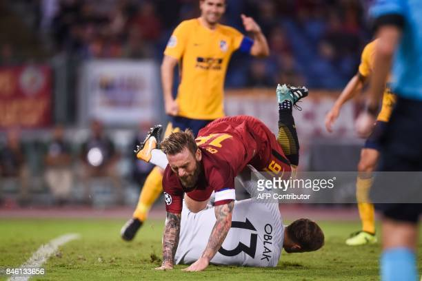 Roma's midfielder Daniele De Rossi stumbles over Atletico Madrid's Slovenian goalkeeper Jan Oblak during the UEFA Champions League Group C football...