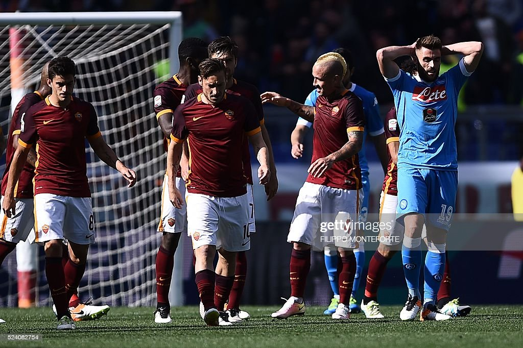 Roma's midfielder from Belgium Radja Nainggolan (2ndR) celebrates with teammate Roma's forward Francesco Totti after scoring during the Italian Serie A football match AS Roma vs Napoli on April 25, 2016 at the Olympic Stadium in Rome.