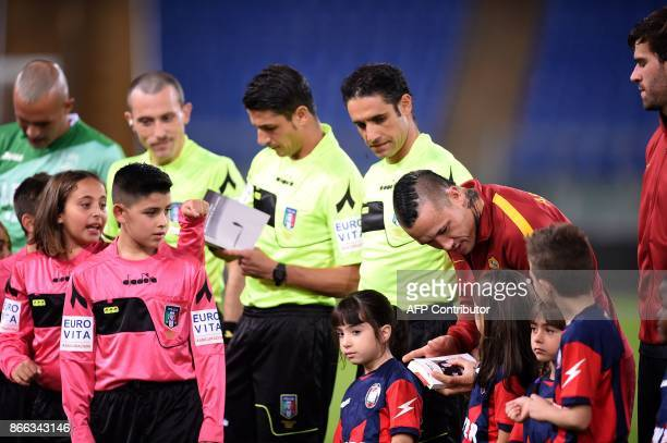 Roma's midfielder from Belgium Radja Nainggolan holds the book of holocaust victim Anne Frank before the Italian Serie A football match AS Roma vs...