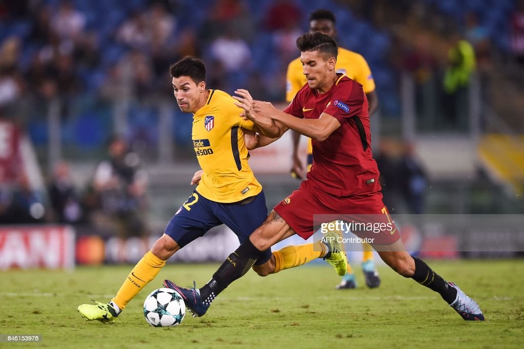 Roma's midfielder Lorenzo Pellegrini (R) tackles Atletico Madrid's Argentinian midfielder Nicolas Gaitan during the UEFA Champions League Group C football match between AS Roma and Atletico Madrid on September 12, 2017 at the Olympic stadium in Rome. / AFP PHOTO / Filippo MONTEFORTE